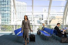 Businesswoman walking in airport departure lounge with luggage in tow, businessman reading newspaper Royalty Free Stock Photo