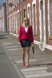 Businesswoman walking along sidewalk in residential area Royalty Free Stock Image