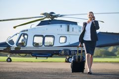 Businesswoman Walking Away From Helicopter Whilst Talking On Mob stock photo
