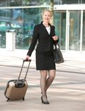 Businesswoman walking in the city with luggage Stock Photo