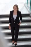 Businesswoman walking down stairs Royalty Free Stock Image