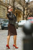 Businesswoman walking down the street while talking on smart pho Royalty Free Stock Images
