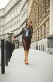 Businesswoman walking down the street while talking on smart pho Stock Photos