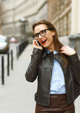 Businesswoman walking down the street while talking on smart pho Stock Images