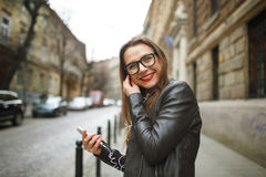 Businesswoman walking down the street while using the smart phon Royalty Free Stock Image