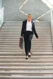 Businesswoman walking downstairs with briefcase Royalty Free Stock Photography