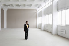 Businesswoman Walking In Empty Warehouse Stock Photo
