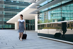 Businesswoman walking with her luggage Royalty Free Stock Photos