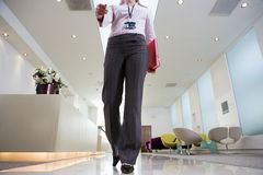 Businesswoman walking through lobby, carrying pink folder, low section, front view, surface level Royalty Free Stock Image