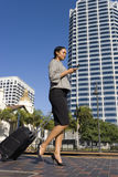Businesswoman walking with luggage in urban setting Royalty Free Stock Images