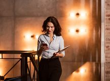 Businesswoman walking at modern restaurant with laptop and checking her smart phone. Handsome elegant caucasian businesswoman walking at modern restaurant with Royalty Free Stock Image