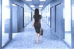 Businesswoman walking in the office corridor stock image