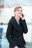 Businesswoman walking outdoors and talking on the phone Royalty Free Stock Image