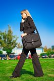 Businesswoman walking in the park Royalty Free Stock Image