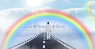 Businesswoman walking on road with surreal time clocks perspective and rainbow. Digital composite of Businesswoman walking on road with surreal time clocks Royalty Free Stock Photos