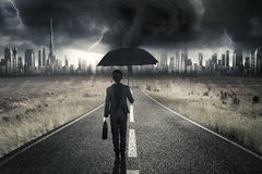 Businesswoman walking on road with thunderstorm Stock Photography
