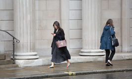 Businesswoman  walking on the street against of Bank of England wall. LONDON, UK - SEPTEMBER 17, 2015: Businesswoman  walking on the street against of Bank of Royalty Free Stock Image