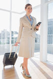 Businesswoman walking with suitcase and checking her phone Royalty Free Stock Photos