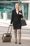 Businesswoman walking with suitcase int he city Stock Photos