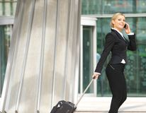 Businesswoman walking with suitcase and talking on mobile phone Stock Photos