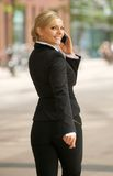 Businesswoman walking and talking on cellphone Stock Photo
