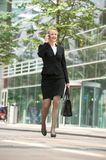 Businesswoman walking and talking on mobile phone in the city Royalty Free Stock Photography