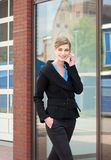 Businesswoman walking and talking on mobile phone Stock Image