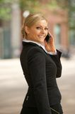 Businesswoman walking and talking on mobile phone Stock Images