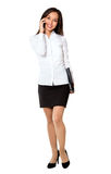 Businesswoman walking talking on mobile phone. Stock Photography