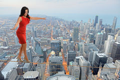 Businesswoman Walking on Tightrope Stock Photography