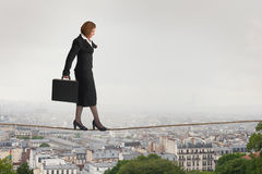 Businesswoman walking a tightrope Stock Images