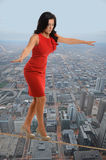 Businesswoman Walking on Tightrope Stock Image