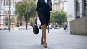 Businesswoman walking to work and using smartphone, busy lifestyle in big city stock photography
