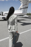 Businesswoman Walking Towards Private Airplane Stock Images