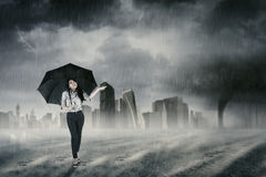 Businesswoman walking with umbrella in rain Royalty Free Stock Photography