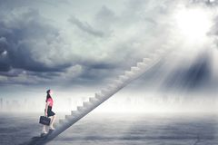 Businesswoman walking up staircase to door in sky with bright light shining down.  Royalty Free Stock Images