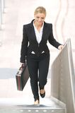 Businesswoman walking upstairs with briefase Stock Photo