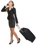 Businesswoman walking with wheeled suitcase Royalty Free Stock Photography