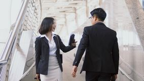 Businesswoman was greetings the businessman while going in oppos. Close up Asian female traveler or businesswoman route inquiry from a young businessman with map Royalty Free Stock Images