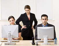 Businesswoman watching co-workers work Stock Images