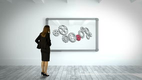 Businesswoman watching cog and wheel on wall. Digital animation of Businesswoman watching cog and wheel on wall stock video footage