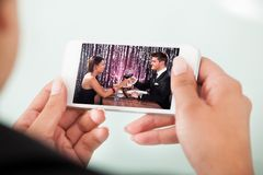Businesswoman watching couple toasting wineglasses on cellphone. Cropped image of businesswoman watching couple toasting wineglasses on cellphone over white Royalty Free Stock Photography