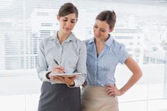 Businesswoman watching her colleague write on clipboard. Standing in their office Stock Photos