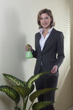 Businesswoman watering plants Royalty Free Stock Image