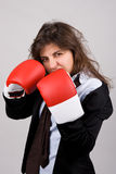 Businesswoman wearing boxing gloves Stock Photography