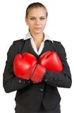 Businesswoman wearing boxing gloves, arms crossed Royalty Free Stock Photo