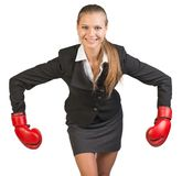 Businesswoman wearing boxing gloves bending Stock Photography