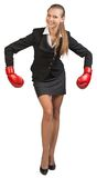 Businesswoman wearing boxing gloves bending Royalty Free Stock Images