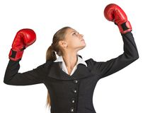 Businesswoman wearing boxing gloves, with her arms Stock Images