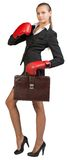 Businesswoman wearing boxing gloves holding Royalty Free Stock Images